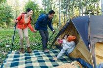 Genitori felici con bastoni da trekking guardando i bambini adorabili che riposano in tenda nella foresta — Foto stock