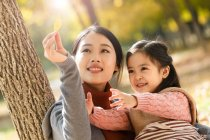 Feliz asiático mãe e filha olhando outono folha no parque — Fotografia de Stock
