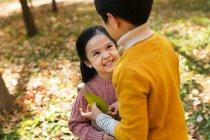 Alto angolo vista di felice carino asiatico bambini giocare insieme in autunno parco — Foto stock