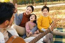 Ritagliato colpo di padre che suona la chitarra e la famiglia felice seduta su plaid nel parco autunnale — Foto stock