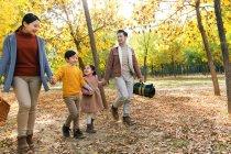 Famille heureuse avec panier pique-nique tenant la main et marchant dans la forêt d'automne — Photo de stock