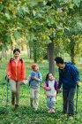 Glückliche junge Familie mit Rucksäcken und Trekkingstöcken im Wald — Stockfoto