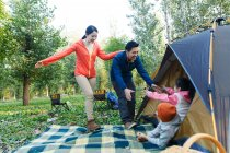 Genitori felici guardando i bambini adorabili che riposano in tenda nella foresta — Foto stock