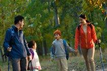 Familia asiática joven feliz con mochilas y trekking pega caminatas en bosque - foto de stock
