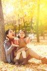Feliz asiático mãe e filha sentado perto de árvore e brincando com folhas no parque — Fotografia de Stock