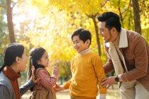 Felici giovani genitori asiatici guardando adorabili bambini sorridenti nella foresta autunnale — Foto stock