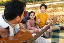 Madre con bambini adorabili guardando il padre che suona la chitarra in primo piano nella foresta — Foto stock