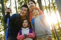 Низкий угол зрения счастливой семьи с рюкзаками походы и глядя вместе в осеннем лесу — стоковое фото