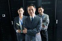 Personale tecnico che sorride alla telecamera mentre lavora nell'ispezione della sala di manutenzione — Foto stock