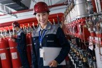 Ingénieurs professionnels masculins et féminins dans les chapeaux durs travaillant dans l'inspection de la salle de contrôle du feu usine — Photo de stock