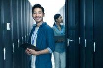 Operaio maschio sorridente alla macchina fotografica mentre ingegnere donna che lavora nel controllo della sala di manutenzione — Foto stock