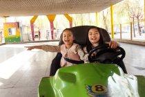 Милые веселые китайские девушки верхом на машине и играть вместе на детской площадке — стоковое фото