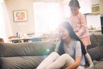 Feliz joven madre sentada en el sofá y la hija pequeña de pie detrás - foto de stock