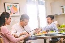 Famille asiatique heureuse avec un enfant s'asseyant à la table et mangeant ensemble — Photo de stock