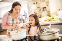 Happy asian mother and daughter cooking together in kitchen — Stock Photo