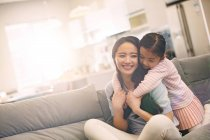 Mãe asiática nova feliz com a filha pequena adorável que abraça junto no sofá — Fotografia de Stock