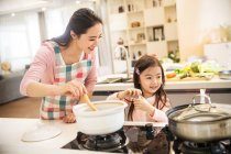 Happy asian mother and daughter cooking soup together in kitchen — Stock Photo