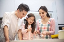 Happy asian family with one child cooking together in kitchen — Stock Photo