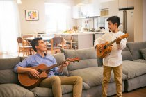 Happy asian father and son playing guitars and smiling each other at home — Stock Photo