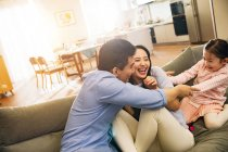 Happy parents with adorable little daughter having fun together on couch — Stock Photo