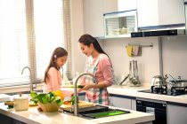 Happy young mother and cute little daughter cooking together in kitchen — Stock Photo