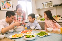 Happy chinese family with two children eating together at home — Stock Photo
