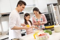 Happy parents with adorable little daughter cooking together in kitchen — Stock Photo