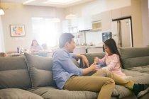Feliz padre con adorable hijita sentada y jugando juntos en el sofá - foto de stock