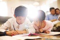 Adorables enfants chinois faisant leurs devoirs à la maison, parents assis derrière — Photo de stock