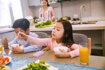 Adorable asian brother and sister having breakfast together while mother cooking behind in kitchen — Stock Photo