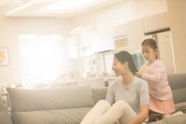 Adorable little daughter plaiting braid to smiling young mother sitting on couch — Stock Photo