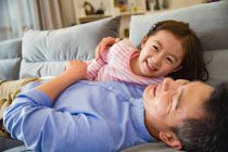 Happy asian father and cute little daughter playing and having fun together on couch — Stock Photo