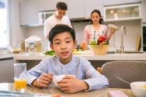 Милый китайский мальчик сидит за столом и смотрит в камеру, родители стоят позади на кухне — стоковое фото