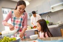 Sonriendo joven madre vertiendo leche a adorable hija en la cocina - foto de stock