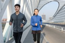 Smiling young male and female athletes running on bridge — Stock Photo