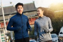 Happy young asian couple of runners training together on street in the morning — Stock Photo