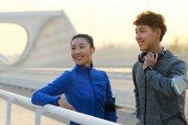 Улыбающаяся молодая азиатская пара в спортивной одежде, стоящая на мосту и отворачивающаяся после тренировки — стоковое фото