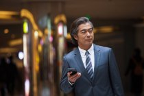 Front view of confident mature asian businessman in formal wear holding smartphone and looking away — Stock Photo