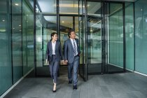 Asian business people walking in modern business center — Stock Photo