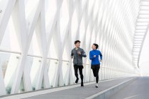 Sporty young couple smiling each other and running together on bridge — Stock Photo