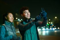 Happy sporty young asian couple taking selfie with smartphone during workout at night — Stock Photo