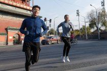 Sporty young smiling asian couple running together on street — Stock Photo