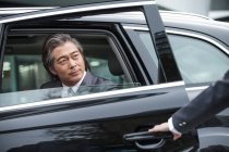 Cropped shot of someone opening car door to serious mature businessman — Stock Photo