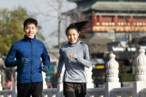 Front view of young asian athletes smiling at camera and jogging together on street — Stock Photo