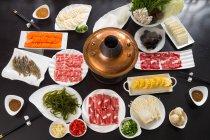 Vue à angle élevé de divers ingrédients, viande, légumes, fruits de mer et pot chaud de cuivre, concept de plat de frottement — Photo de stock