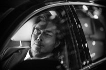 Close-up view of pensive mature asian man sitting in car, black and white image — Stock Photo