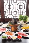 High angle view of various ingredients on plates and copper hot pot, chafing dish concept — Stock Photo