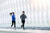 Sportif jeune asiatique couple sourire l autre et courir ensemble sur pont — Photo de stock