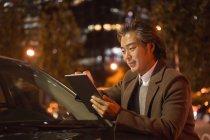 Sorridente maturo uomo asiatico in piedi accanto alla macchina e utilizzando tablet digitale di notte — Foto stock