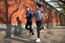 Joven asiático pareja sonriendo uno a otro y corriendo juntos en calle - foto de stock
